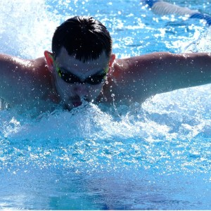 Pływak w okularach pływający w błękitnej wodzie
