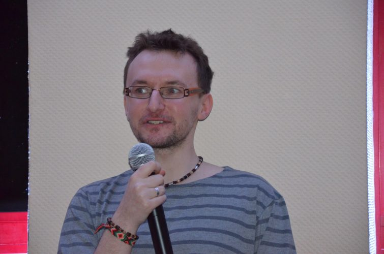 Mężczyzna z brodą i w okularach trzyma mikrofon