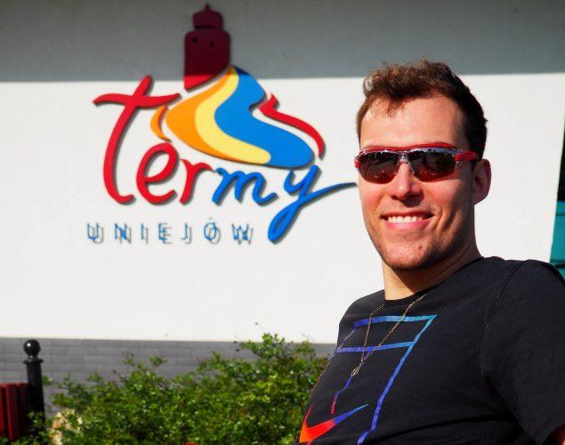Mężczyzna w okularach, w tle logo Term Uniejów