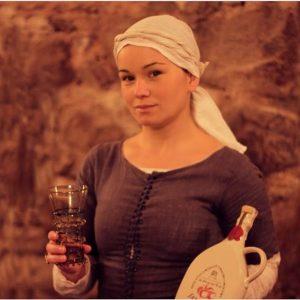 Dziewczyna w dawnym stroju pokazuje butelkę miodu pitnego i kieliszek