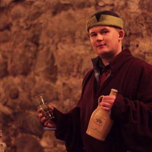 Mężczyzna w dawnym stroju proezentuje butelkę miodu pitnegoi kieliszek