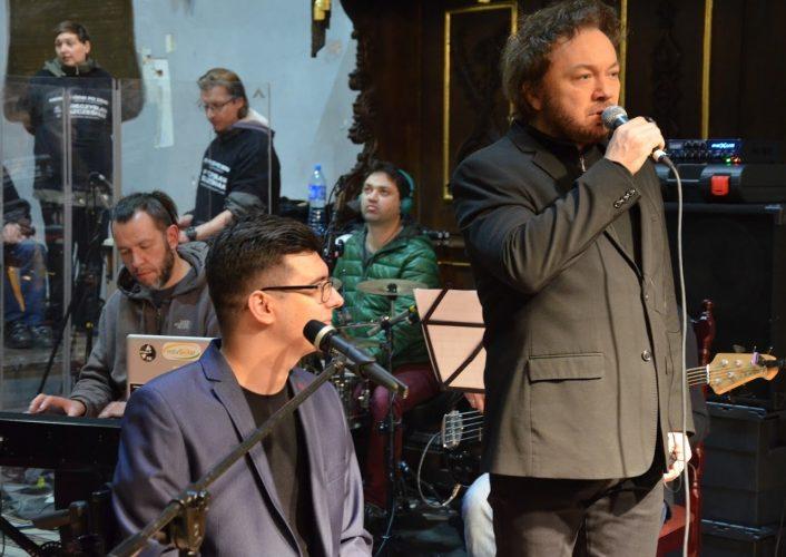 Mężczyzna ubray na ciemno śpiewa do mikrofonu. Obok muzycy