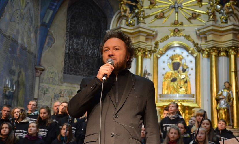 Mężczyzna z mikrofonem przy ustach, w tyle zespół muzyczny i pozłacany ołtarz