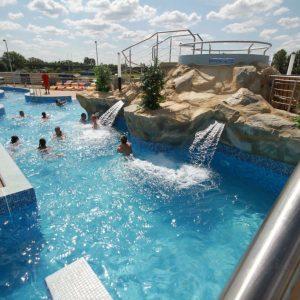 basen z błękitna wodą i urządzeniami do masaży wodnych