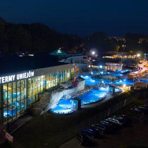 """Oświetlony kompleks basenowy w porze wieczornej. Na budynku napis """"Termy Uniejów""""rz"""