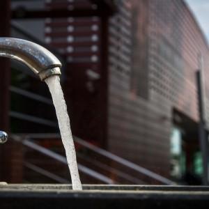 woda leci z kranu, w tle budynej