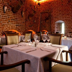 Nakryte stoły w zabytkowym wnętrzu restauracji. Na ścianach z czerwonej cegły wiszą trofea myśliwskie