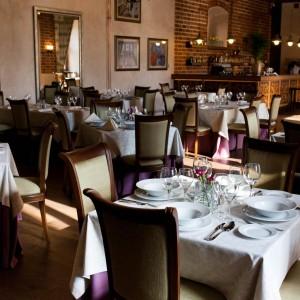 Nakryte stoły w restauracji znajdującej sie w zabytkowym wnetrzu i