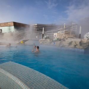 Mężczyźni kąpiący się w parującej wodzie. W głębi jasny budynek