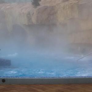 Parująca woda w basenie. W tle jasne skały