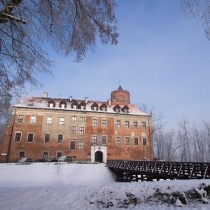 Zamek z czerwonej cegły w okresie zimowym. Do zamku prowadzi drewniany most