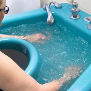 kobieta zanurza rece w wodzie
