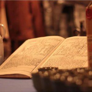 Stara księga rozłożona na stole, obok butelka miodu pitnegi