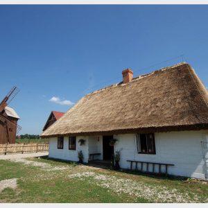 Chata kryta strzechą, na drugim planie wiatrak