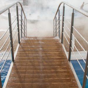 Drewniany mostek z metalowymi poręczami. W głębi parująca woda