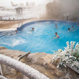 Ludize kąpiący się zimą w basenach. Na pierwszym planie osztoniona balustrada i rośliny