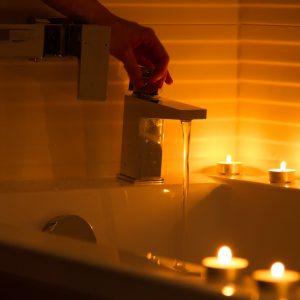 Dłoń odkręca kurek z wodą, która leje się do wanny. Na brzegu wanny poustawiane świeczki ku
