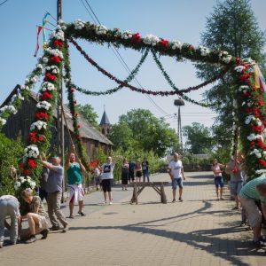 Grupa osób ustawia bramę przystrojoną kwiatami