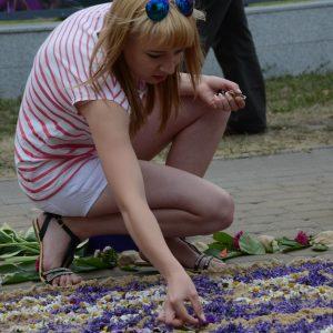Dziewczyna układa na ziemi wzór z żywych kwiatów